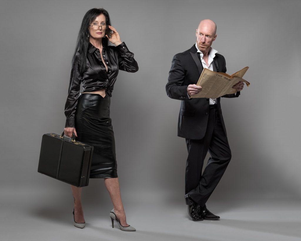femme avec valise regardée par homme avec journal