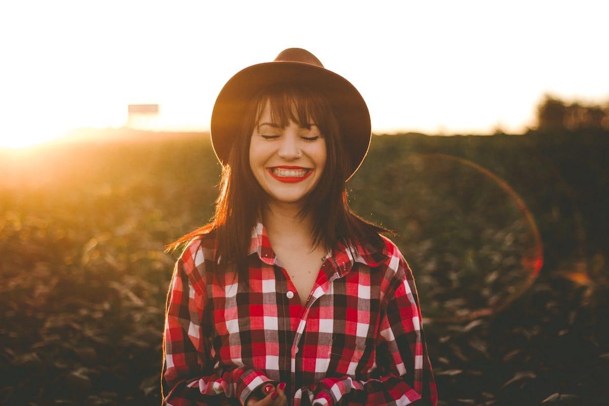 femme souriant au coucher du soleil