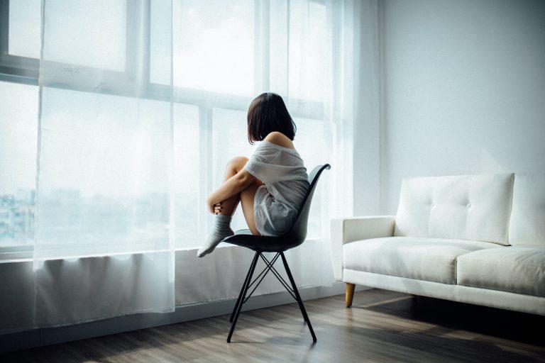 fille seule assise devant fenêtre